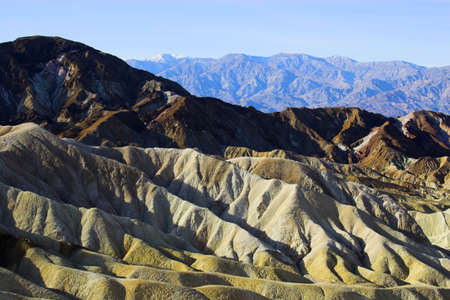 Desert landscape with multicolored yellow clay and salt mineral deposits in geological formations of Death Valley National Park photo
