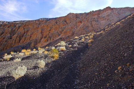 volcanic stones: Fragment of black lava and ornage clay and salt mineral deposits in geological formations in Ubehebe Volcano, Death Valley National Park