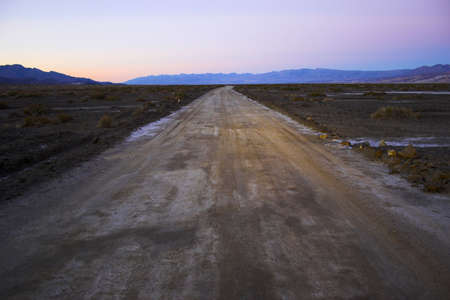 Desert road going through mineral deposits and geological formations of Death Valley National Park photo