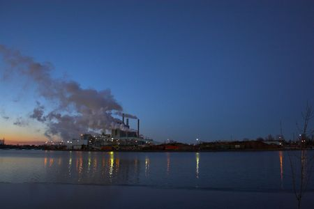 Factory over the river with smoke coming out of the chimneys photo
