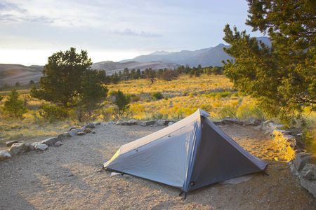 Camping and tent  at oasis in great sand dunes during sunset  photo