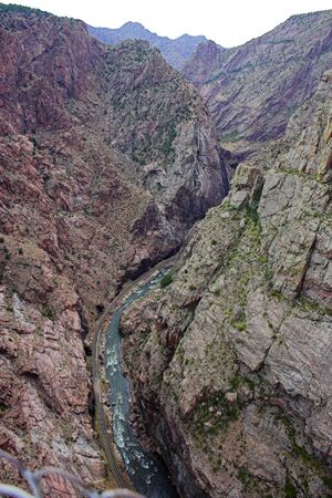View down from the top of Royal Gorge canyon, kayakers in the mountain stream
