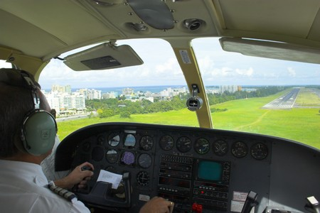 Small plane pilot flying and landing over tropical island in\ Caribbean