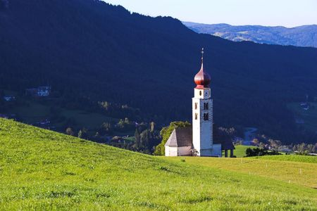 Beautiful chapel in the green meadows of Alps, Italy photo