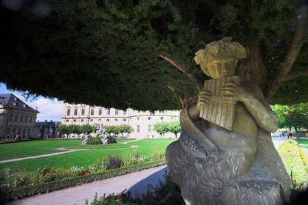 residence: Stone statue of angel under tree in Wurzburg Residence gardens