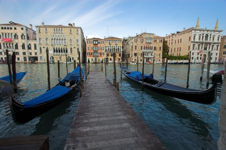 Row of gondolas moored on Grand Canal in Venice photo