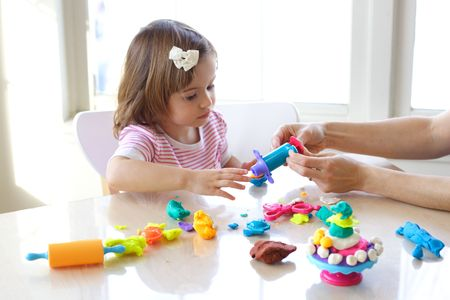 Hands of young woman show little girl how to use play dough Stock fotó