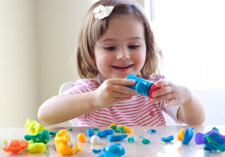 Little girl is learning to use colorful play dough in a well lit room near window