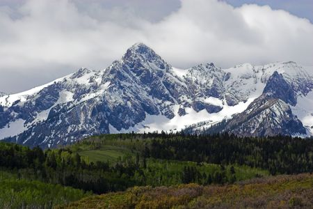 colorado mountains: Rolling green hills and snow covered mountain peaks in Colorado