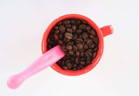 The cup full of coffee beans on light background  photo