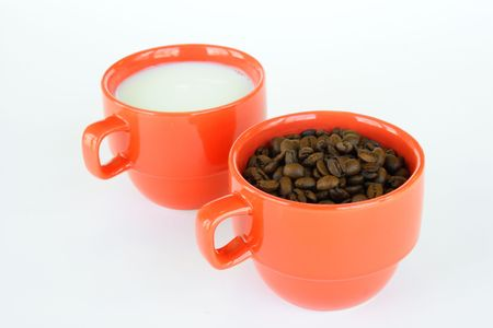 The cups full of coffee beans and milk on light background  photo