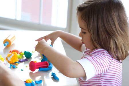 Little girl is learning to use colorful play dough in a well lit room near window photo