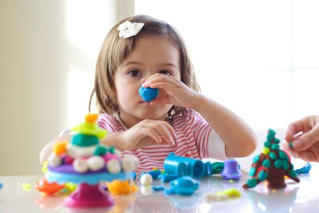 Little girl is learning to use colorful play dough in a well lit room near window Stock Photo - 6679640