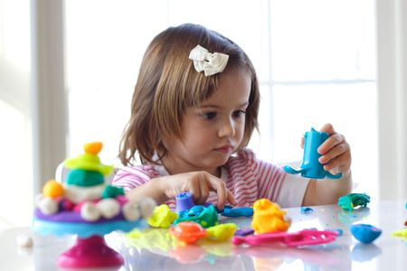 clay: Little girl is learning to use colorful play dough in a well lit room near window