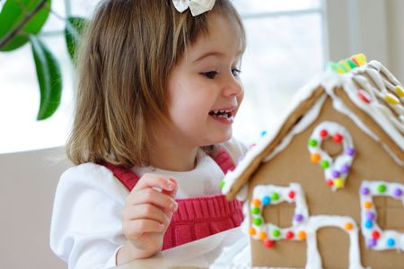 Little girl decorating gingerbread house and treating herself to candy photo