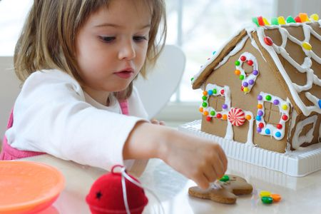 decorating: Little girl decorating gingerbread house for Christmas