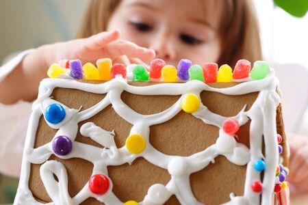 toiture maison: Fragment de toit de la maison en pain d'�pice parsem� de bonbons color�s et le visage petite fille sur fond