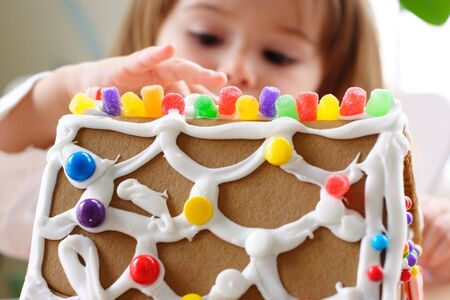 Fragment of gingerbread house roof dotted with colorful candy and little girl face on background Stock Photo