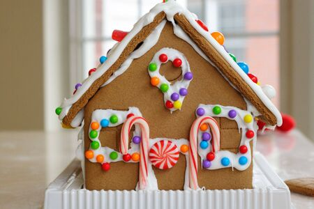 Gingerbread cookie house dotted with colorful candy photo