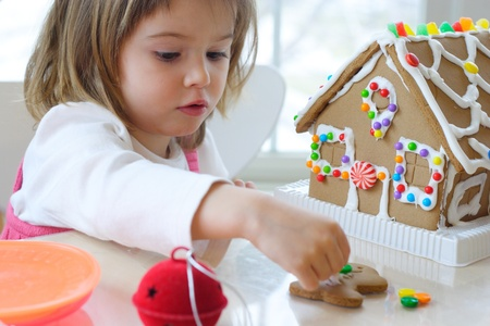 christmas gingerbread: Little girl decorating gingerbread house for Christmas
