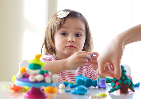 Hands of young woman show little girl how to use play dough Stock Photo