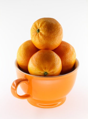 Orange tangerine fruit arranged in a cup photo