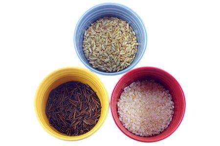 Diversos tipos de arroz en blancos sobre fondo coloridas tazas Foto de archivo - 8387033
