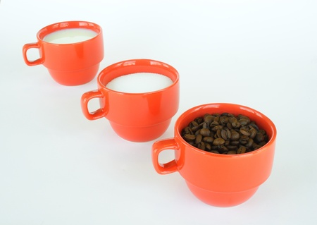The cups full of coffee beans sugar and milk on light background  photo