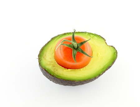 Cross section of avocado with cherry tomato inside