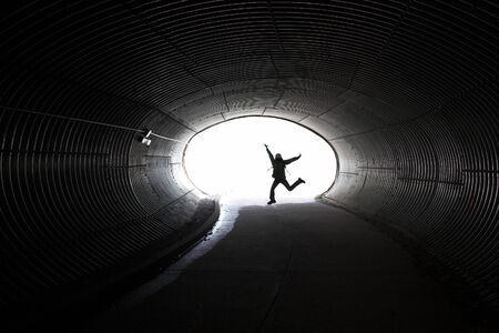Jumping girl silhouette inside dark long tunnel