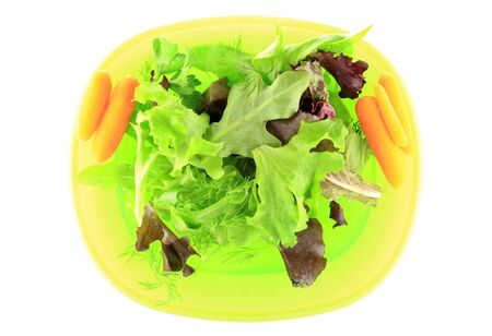 Fresh baby lettuce and herbs on yellow plate with white background