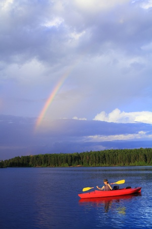 Woman canoeing in a beautiful lake with rainbow in the sky photo
