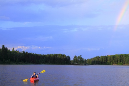 Woman canoeing in a beautiful lake with rainbow in the sky