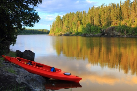 Red canoe sitting on the rocks at the lake in Minnesota, USA 스톡 콘텐츠