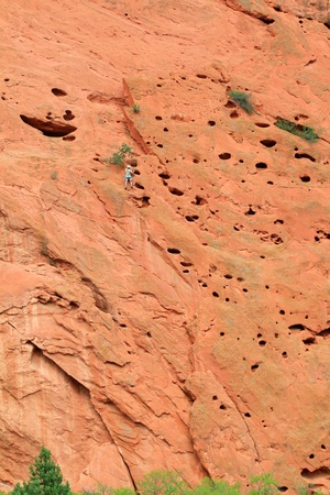 Person climbing the unusual rock formation in Garden of the Gods, Colorado, USA