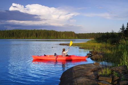 日没の美しい湖でカヌーの女性 写真素材