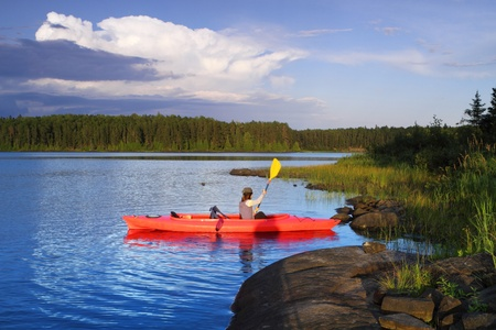 Woman canoeing in a beautiful lake at sunset Stock Photo - 12382191