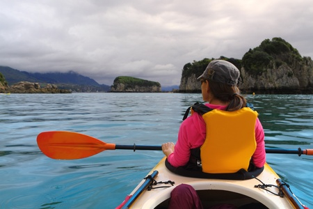 Family ocean kayaking among limestone cliffs in a beautiful Abel Tasman National Park in New Zealand