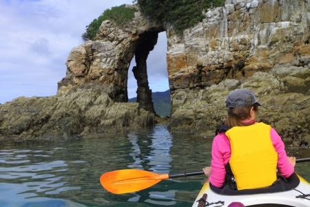 Family ocean kayaking among limestone cliffs in a beautiful Abel Tasman National Park in New Zealand photo