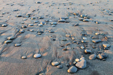 Beautiful pebble pattern on wet sand on the beach photo