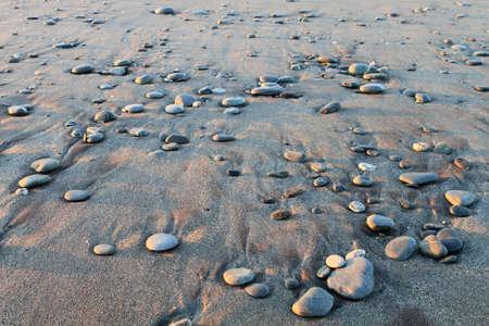 Beautiful pebble pattern on wet sand on the beach