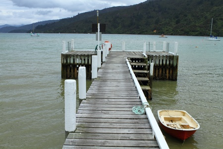 Boat moored at the dock along the scenic Queen Charlotte drive, Marlborough Region, New Zealand photo