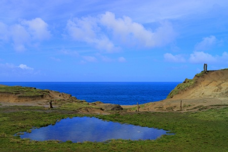 Sandy outcrop and blue ocean in Catlins, New Zealand photo