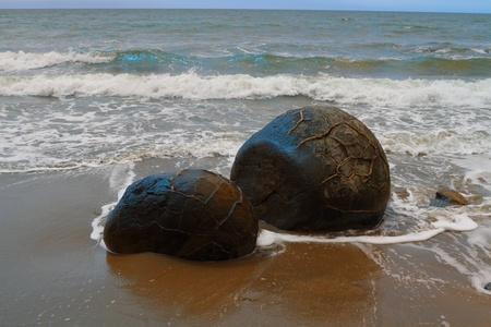 Unusually large and spherical Moeraki boulders lying along the beach on Otago coast, New Zealand