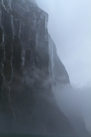 Hundreds of waterfalls flowing from the mountains during the rainstorm in Fiordland National Park, New Zealand photo