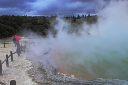 A tourist observing a beautiful volcanic hot spring in Rotorua, New Zealand