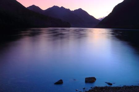 Beautiful mountain lake during sunset in Fiordland National Park, South Island, New Zealand photo