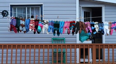 A colorful row of woolen knitted socks displayed for sale in a village photo