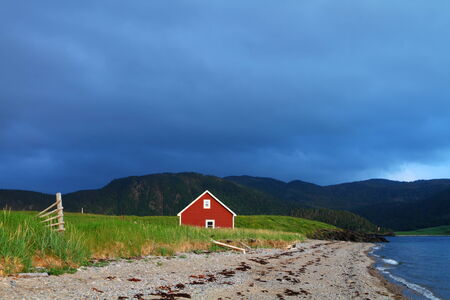 Red wooden cabin on the shore in Nordic landscape