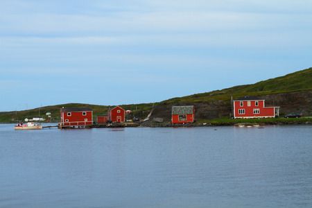 Red cottages and boat in fishing village in Nordic landscape photo